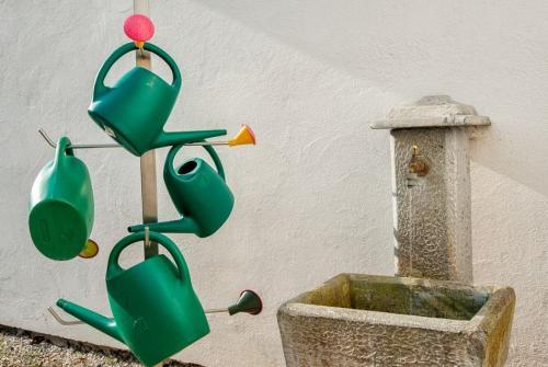 Na sliki je fontana in zalivalke na pokopališču.