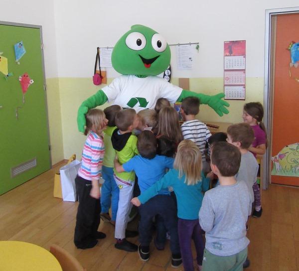 Na sliki je maskota Grini z otroki.