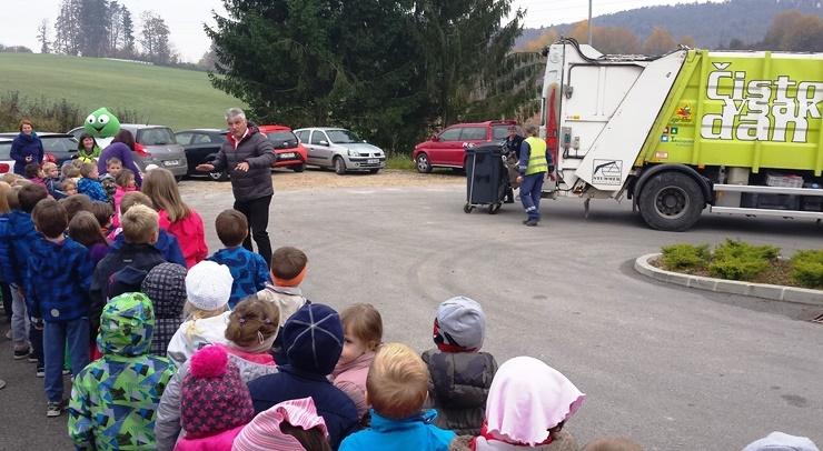 Slika prikazuje otroke, ki si ogledujejo praznjenje zabojnikov s smetarskim vozilom.