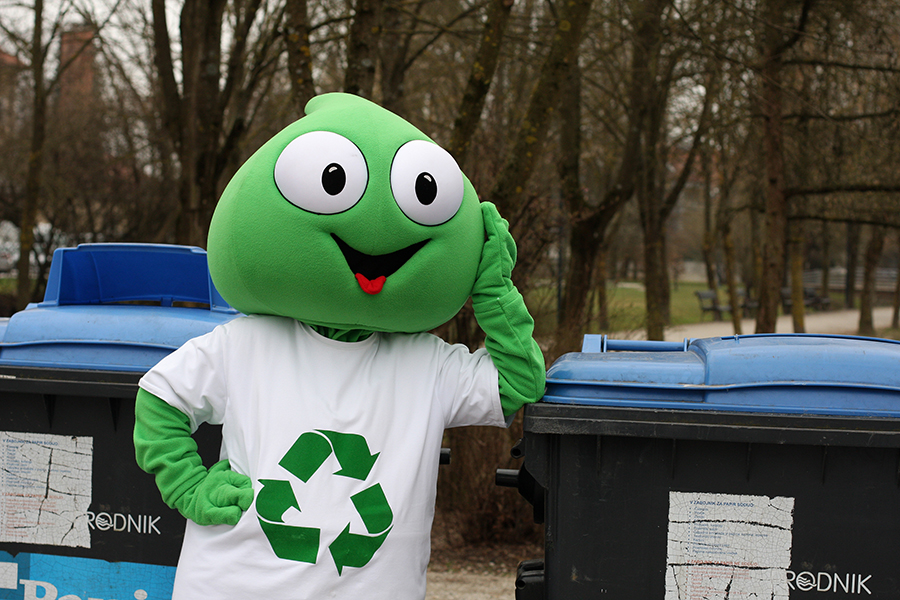 Na sliki je maskota Grini ob zabojniku za ločeno zbiranje papirja.