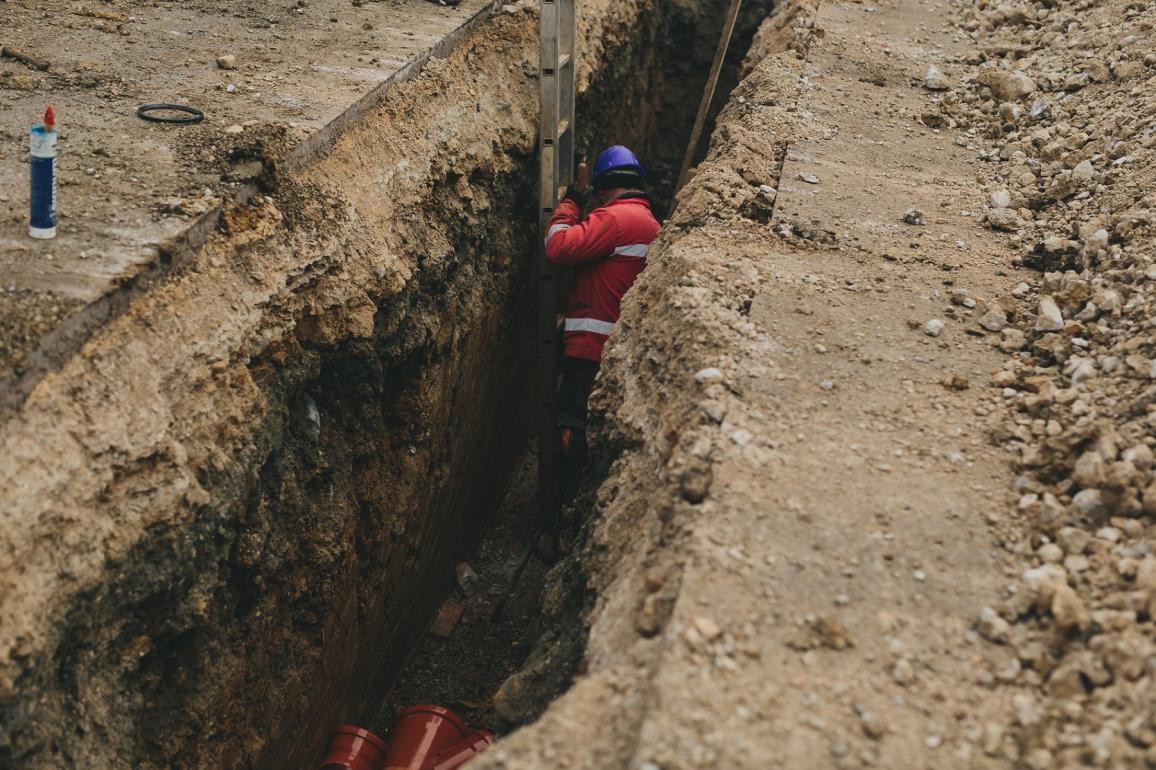 Slika prikazuje delavca pri izvajanju polaganja cevi.