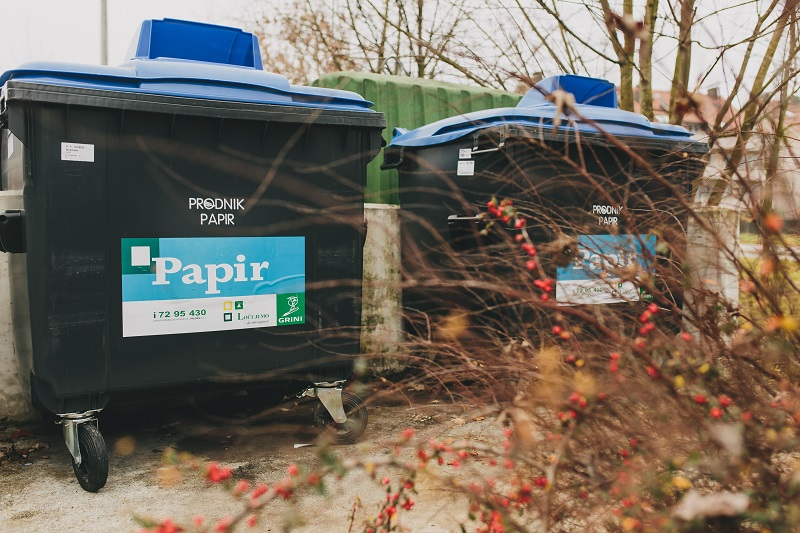 Slika prikazuje zabojnika za papir na ekološkem otoku.