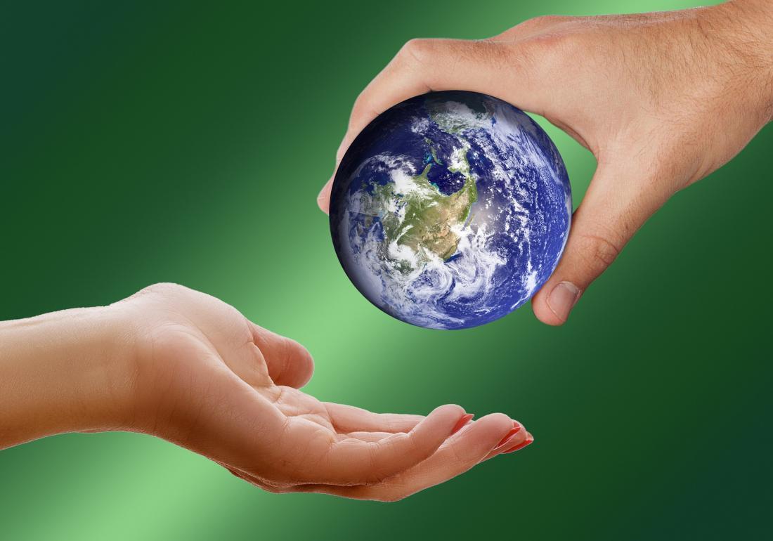 Slika prikazuje planet Zemljo v človeških rokah.